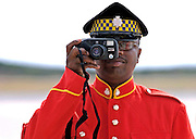 Soldier from the Jamaica Defence Force taking a photograph using a compact camera with zoom lens, Kingston, Jamaica