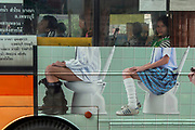 Public bus passengers unaware of their role in a surreal moment of everyday life in Bangkok