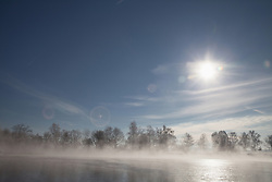 Sun shining over lake in winter, Eichenau, F¸rstenfeldbruck, Bavaria, Germany