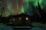 The northern lights shine over a cabin outside of Fairbanks, Alaska