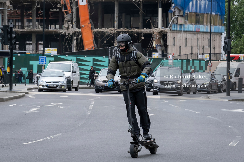 An eScooter rider wearing goggles over his face and a helmet protecting his head, speeds ahead of traffic, on 22nd June 2021, in London, England.