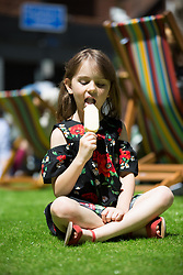 EDITORIAL USE ONLY<br /> Lily Roake, 5, from Windsor relaxes on a lawn laid in Seven Dials, central London for the Seven Dials Fashion Feast event.