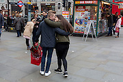 A young man with a bouquet of red roses gets a kiss from his girlfriend, on 15th February 2017, in Piccadilly Circus, London borough of Westminster, United Kingdom.