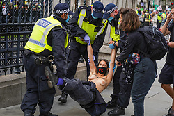 © Licensed to London News Pictures. 10/09/2020. A topless protester has been arrested this afternoon in Central London. Topless protesters have made a chain into the railings of Parliament during a climate change protest by the group Extinction Rebellion.  Photo credit: Ioannis Alexopoulos/LNP