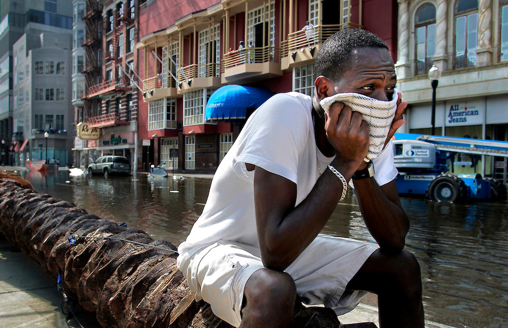 Rodney Thomas, 41, of New Orleans sits on a downed tree while waiting for a ride out of town Wednesday, August 31, 2005, on Canal Street in the French Quarter of New Orleans, La. Thomas rode out Hurricane Katrina in uptown New Orleans and came downtown to see what was left of the city. Scott Morgan