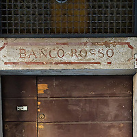 "VENICE, ITALY - NOVEMBER 15:  A sign displayed on a wall shows the entrance to the ""Banco Rosso"" one of the three money lenders that used to operate during the middle ages on November 15, 2011 in Venice, Italy. Established in 1516 the Ghetto of Venice was the area were Jews were compelled to live during the Venetian Republic. The English term 'ghetto' is derived from the Venetian term for 'slag' and refers to the refuse left the foundry that was located on the same island. In present times the ghetto is a multi-ethnical area area seen as the cultural heart of the city, but with five synagogues remains the centre of the of Jewish community."