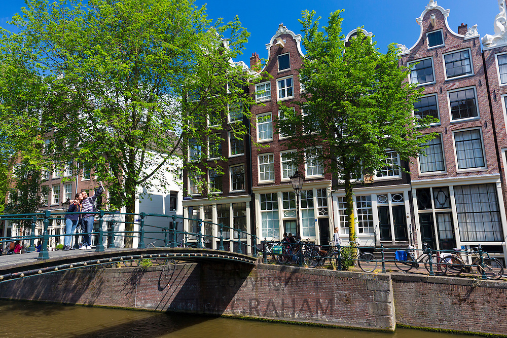 Tourists taking selfie photograph with smartphone on Milkmaid's Bridge Melkmeisjesbrug on Brouwersgracht, Amsterdam, Holland