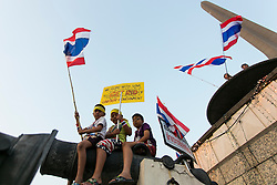 © Licensed to London News Pictures. 16/01/2014. Young Childern wave Thai Flags while one child holds up a banner reading 'We Come with love to get rid of unfair government' during the fourth day of the 'Bangkok Shutdown' as anti-government protesters continue with their 'shutdown' of Bangkok.  Major intersections in the heart of the city have been blocked in their campaign to oust Prime Minister Yingluck Shinawatra and her government in Bangkok, Thailand. Photo credit : Asanka Brendon Ratnayake/LNP