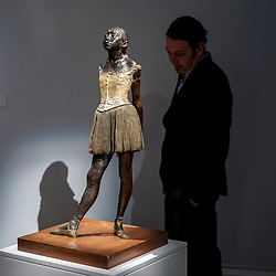 "© Licensed to London News Pictures. 19/06/2015. London, UK. A man views Edgar Degas' bronze, ""Petite danseuse de quatorze ans"", (est. £10m-£15m), at Sotheby's Impressionist, Modern & Contemporary Art preview, ahead of the sale on 24 June 2015. Leading the sale are Kazimir Malevich's, ""Suprematism, 18th Construction"" and Edouard Manet's ""Le Bar aux Folies-Bergère"".  Photo credit : Stephen Chung/LNP"