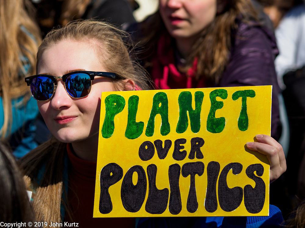 """15 MARCH 2019 - ST. PAUL, MINNESOTA, USA: A high school student holds a """"Planet Over Politics"""" sign during the MN Youth for Climate Justice """"Climate Strike"""" at the Minnesota State Capitol in St. Paul, MN. Thousands of high school students braved below freezing temperatures and biting winds to demand action on climate change. The Minnesota Climate Strike was inspired by the strike by Greta Thunberg, a Swedish high school student, who started a climate strike at her school in August 2018.        PHOTO BY JACK KURTZ"""