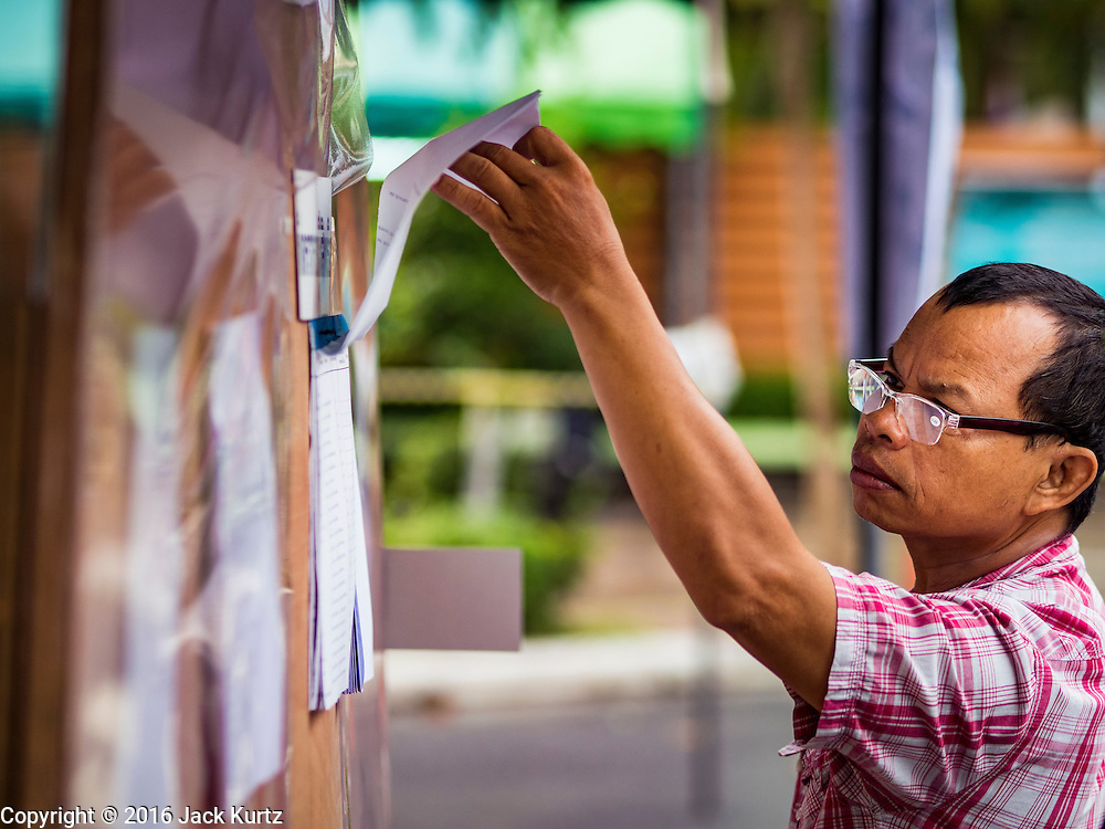 07 AUGUST 2016 - BANGKOK, THAILAND: A man looks for his name on voting rolls at a polling place at Wat That Thong in Bangkok. Thais voted Sunday in the referendum to approve a new charter (constitution) for Thailand. The new charter was written by a government appointed panel after the military coup that deposed the elected civilian government in May, 2014. The charter referendum is the first country wide election since the coup.      PHOTO BY JACK KURTZ
