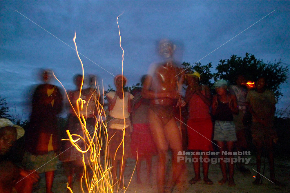 Namibia, 2004 - Bushmen performs traditional songs around the fire while members of his village clap the rhythms behind him.