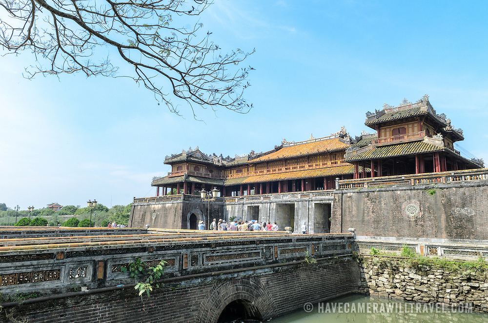 Tourists walk across the bridge over the moat to the Citadel gate at the Imperial City in Hue, Vietnam. A self-enclosed and fortified palace, the complex includes the Purple Forbidden City, which was the inner sanctum of the imperial household, as well as temples, courtyards, gardens, and other buildings. Much of the Imperial City was damaged or destroyed during the Vietnam War. It is now designated as a UNESCO World Heritage site.