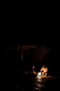 Two men talk by candlelight in the night, Socotra, Yemen