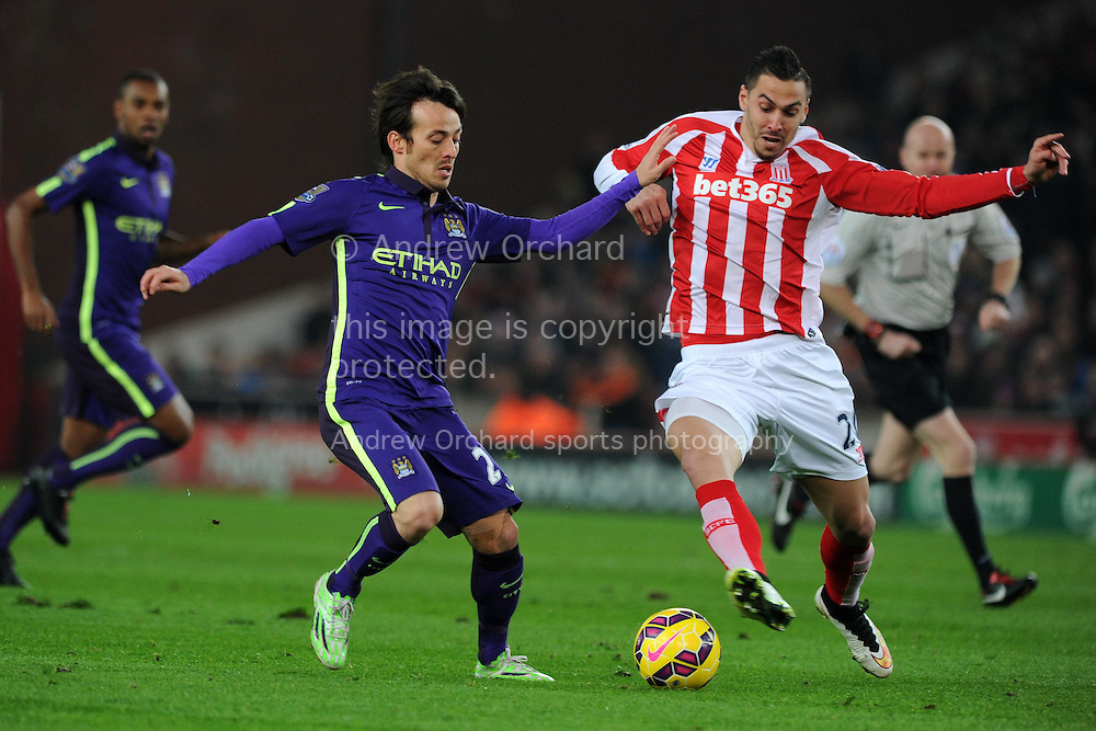 Geoff Cameron of Stoke city ® holds off David Silva of Manchester city. Barclays Premier League match, Stoke city v Manchester city at the Britannia Stadium in Stoke on Trent , Staffs on Wed 11th Feb 2015.<br /> pic by Andrew Orchard, Andrew Orchard sports photography.