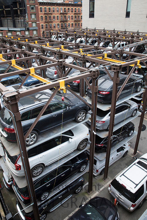 Space-saving automated stacked parking lot with hydraulic lift part of city living and overcrowding in New York City, USA