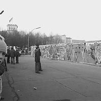 Der Junge kommt aus dem Staunen nicht mehr heraus, ebenso wie die beiden DDR-Grenzpolizisten. In gebührendem Abstand betrachten sie die exotischen Schriftzeichen an der Berliner Mauer, die aus einer für sie fremden Welt stammen. Im Hintergrund Übertragungswagen und eine Kamera des Fernsehens.