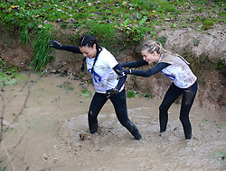 **EXCLUSIVE** ©  London News Pictures. 02/11/2013. Kaya Hall (Girlfriend of Phil Jones, Man U) and Dani Emery (Girlfriend of Ben Amos, Man U) tackle a pool of muddily cold water. Wives and girlfriends of Premiership football players take part in the famous Tough Guy event in Wolverhampton, UK. Mandatory photo credit : Mike King/LNP.
