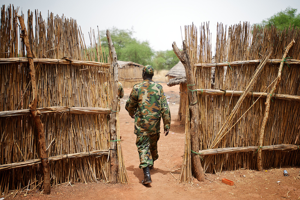 April 24, 2012 - Lalop, South Sudan: A SPLA soldier walks by at the newly established military base in the village o Lalop, 50 kilometers north of Bentiu...South Sudan and their northern neighbors, Sudan, have in the past two weeks been involved in heavily clashes over border disputes. Bentiu and neighboring villages have been under constant bombardment by the troops os Karthoum , who established their positions around 10 kilometers into South Sudan's territory. The international community is concerned about the possibility of a full on war between the two countries. (Paulo Nunes dos Santos/Polaris)