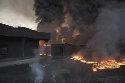October 21, 2016 - Qayyarah, Iraqi-Kurdistan, Iraq - Oil burns in the garden of a home next to several burning wells in a residential neighbourhood in the town of Qayyarah, Iraq. The wells, part of a large oil field that surrounds the town, were set alight by retreating Islamic State militants as part of a scorched earth policy...Since being retaken from the Islamic State the town of Qayyarah has become an important staging post for the Iraqi Army, and some US support elements, in the buildup to the Mosul offensive. (Credit Image: © Matt Cetti-Roberts/London News Pictures via ZUMA Wire)