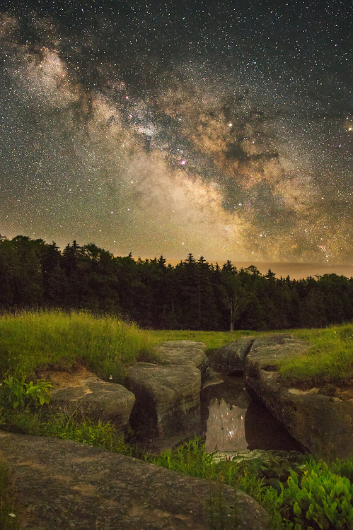 Night time in a country side field strewn with boulders and sink holes in Randolph County, West Virginia, a small section of Earth has parted the ground, cradling within it a deep pool of water filled with aquatic life and lily pads, the mirror-like surface painted with stars reflected from the boundless onyx cosmos above; the still pastoral space between filled with a chorus of frogs and barred owls.