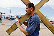 07 AUGUST 2005 - PHOENIX, AZ: DUANE, who lives in the Church of the Street shelter in central Phoenix, carries a cross past the Agape Harvest Church Sunday services in downtown Phoenix Sunday. Ministers from Agape Harvest Church holds weekly church services for street people in Phoenix. They also hand out water and food and distribute clothes. They have been involved in the street ministry for about six months. About 50 people usually attend the service and meals. Agape Harvest Church holds organized services for street people in Phoenix, while Church of the Street walks through downtown Phoenix praying with the homeless.  PHOTO BY JACK KURTZ