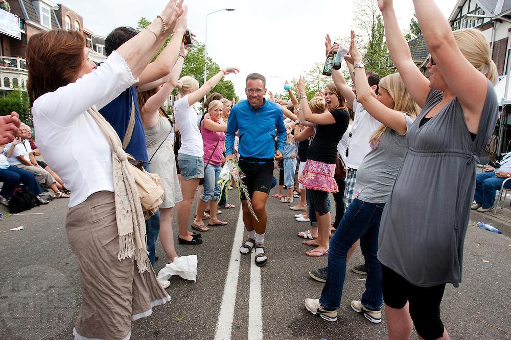 Een wandelaar van de Nijmeegse Vierdaagse loopt op de laatste dag door een erehaag van publiek op de Via Gladiola, zoals de Sint Annastraat is omgedoopt tijdens het wandelevenement.