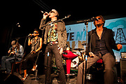Alabama 3 on stage. An event billed as 'We need to talk about Fracking was held at the Rollerdisco venue in London  to raise awareness about fracking. Fracking is a highly controversial method of extracting gas underground. The line-up included Alabama 3 and the Asian Dub Foundation and DJs Gavin Turk and Mark Stewart and Pandit G.