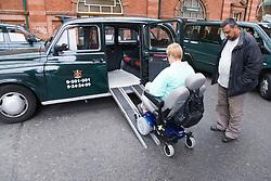 Woman wheelchair user accessing taxi via ramps,