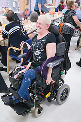 Woman with cerebral Palsy enjoying a friend's birthday party,