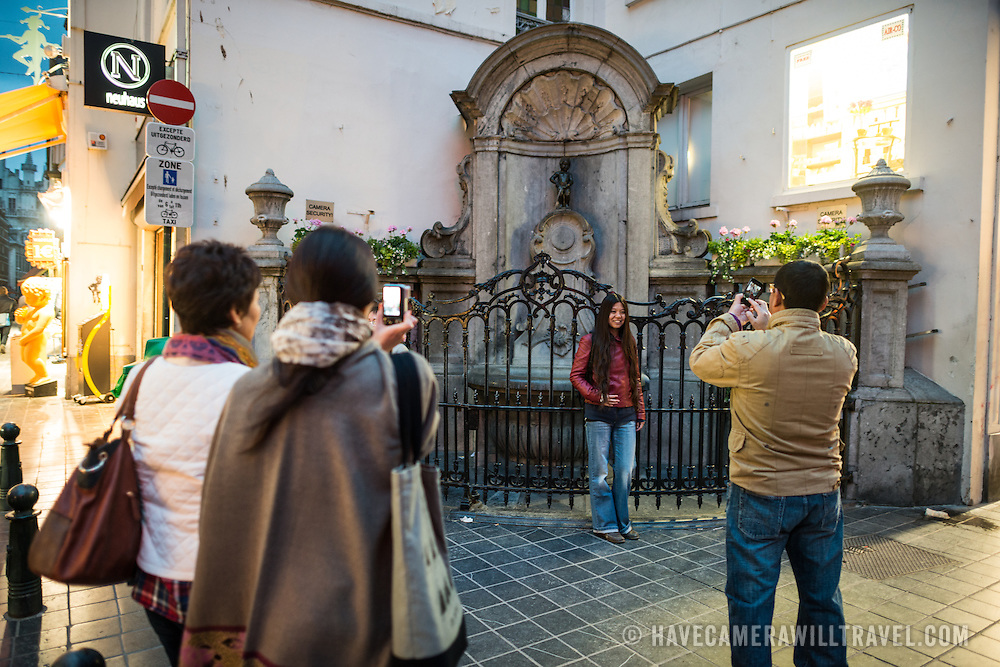 Tourists taking photos in front of the Mannekin Pis, a small bronze fountain sculpture of a naked little boy urinating into the fountain. Installed in about 1619 by Hiëronymus Duquesnoy the Elder, it is a cultural symbol of the city of Brussels and a famous tourism landmark.