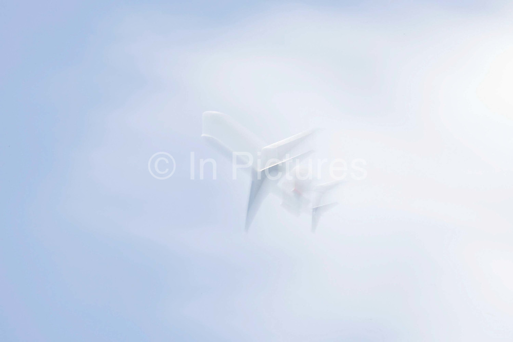 Looking up from the ground to the underside of a jet airliner passing overhead in bright skies, blurred purposely using a slow camera speed, creating a separate, staggered double-image. In slightly hazy skies above south London, where aircraft pass overhead a few thousand feet above suburban homes, the plane is seen as a diagonal, edging across the airspace on its way to the runways at Heathrow airport, approximately 20 miles to the West. The jet is generic, minus airline markings though we see it is a twin-engined model, its two powerplants mounted on the rear section of the fuselage.