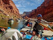 """Rafting through Marble Canyon on day 2 of 16 days boating 226 miles down the Colorado River in Grand Canyon National Park, Arizona, USA. Marble Canyon runs from Lees Ferry at River Mile 0 to the confluence with the Little Colorado River at Mile 62, which marks the beginning of the Grand Canyon. Although John Wesley Powell knew that no marble was found here when he named Marble Canyon, he thought the polished limestone looked like marble. In his words, """"The limestone of the canyon is often polished, and makes a beautiful marble. Sometimes the rocks are of many colors – white, gray, pink, and purple, with saffron tints."""" For this photo's licensing options, please inquire at PhotoSeek.com."""