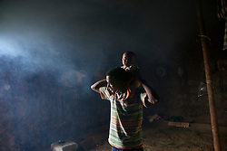 Addisu, 27, stands with his son inside the home he shares with his 15-year-old wife Destaye near Bahir Dar, Ethiopia on Aug. 10, 2012. The couple divide their time between working in the fields and taking care of their 6-month-old baby. Like many other young couples, they tend to the domestic, economic and personal demands of being young parents. At the time of their marriage, when Destaye was age 11, she was still in school and her husband expressed interest in letting her continue her education. Since the birth of their son, however, she has had to confine her life exclusively to being a wife and mother.