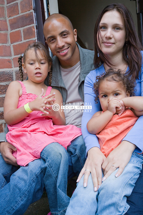 Young family sitting on their doorstep smiling,