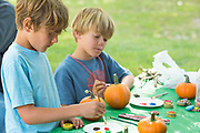 Kids painting pumpkins at the family art table Ritter Island, Thousand Springs Art Festival, Hagerman, Idaho.