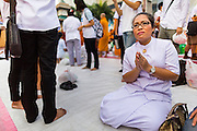 08 SEPTEMBER 2013 - BANGKOK, THAILAND: A woman prays after donating alms to a Buddhist monk during a mass giving ceremony in Bangkok Sunday. 10,000 Buddhist monks participated in a mass alms giving ceremony on Rajadamri Road in front of Central World shopping mall in Bangkok. The alms giving was to benefit disaster victims in Thailand and assist Buddhist temples in the insurgency wracked southern provinces of Thailand.       PHOTO BY JACK KURTZ