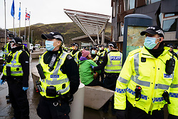 Edinburgh, Scotland, UK. 11 January 2020. Protester arrested in violent scenes at anti lockdown demonstration at Scottish Parliament in Edinburgh today. Several protesters took part but  a heavy and aggressive police presence prevented demonstration and planned march to Bute House. During national Covid-19 lockdown such protests are illegal and police advised people not to attend the demonstration. Pic; Female protester is arrested and bundled into a police van.  Iain Masterton/Alamy Live News