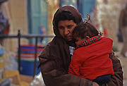 In wintry wind a Palestinian mother holds her child close as she walks on the sidewalk in East Jerusalem.