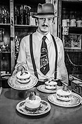 Mozo (waiter) serves strawberry cream cake while wearing Carlos Gardel tie (famous singer/tango dancer  from 1920s) , Ramos Generales cafe, Ushuaia, Argentina.