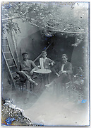 eroding glass plate with men relaxing and drinking beer in backyard