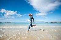 Female traveler runs through cold water of arctic beach, Gimsøy, Lofoten Islands, Norway