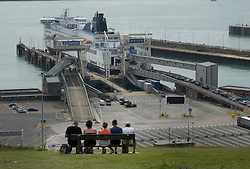 © Licensed to London News Pictures. 23/07/2016. Dover, UK. A family sit on the cliffs overlooking the port of Dover as cars and trucks queue up to enter. Long delays are currently being experienced after increased security checks were put in place. Photo credit: Peter Macdiarmid/LNP