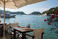 A waterside taverna table in Lakka, Paxos, The Ionian Islands, Greece, Europe