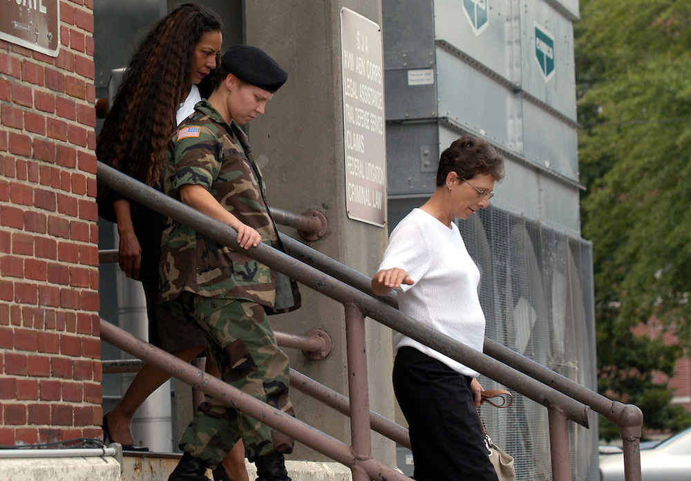 FORT BRAGG, NC- AUGUST 6: Pfc. Lynndie England (Center) returns from a lunch recess with her mother Terrie England (R)  and legal council at the Staff Judge Advocate Building on Fort Bragg in Fayetteville, NC on 8/6/04 for her Article 32 investigation hearing. England is charged with several counts, including one specification of conspiring to commit maltreatment of an Iraqi detainee, three specifications of assault against Iraqis, and several others. (Photo by Logan Mock-Bunting)