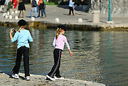 Two children (9 years old, 5 years old) throwing pebbles into water. Korcula old town, island of Korcula, Croatia