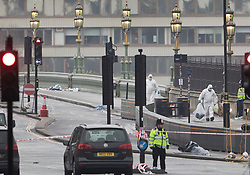 © Licensed to London News Pictures.23/03/2017.London, UK. Forensics officers are seen carrying evidence bags on Westminster Bridge near Parliament, the day after a lone terrorist killed 4 people and injured several more, in an attack using a car and a knife. The attacker managed to gain entry to the grounds of the Houses of Parliament, killing one police officer.Photo credit: Peter Macdiarmid/LNP