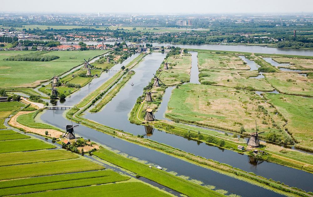 Nederland, Zuid-Holland, Kinderdijk, 04-07-2006; boezems van de polder Nieuw-Lekkerland, onderdeevan de Alblasserwaard; windmolens gebruikt voor het droogmalen van de polder en voor de waterhuishouding (het bemalen); de molens behoren bij het wereld cultureeerfgoed (Unesco); links van de boezem het dorpje Kinderdijk, aan de andere kant van de rivier de Lek , aan de horizon Krimpen aan de IJsse(met hoogbouw); Windmills for pumping the water out of the polder (the drainage). The Mill Network at Kinderdijk-Elshout is part of the  World Heritage of Unesco. More pics available of this location..luchtfoto (toeslag); aerial photo (additional fee required); .foto Siebe Swart / photo Siebe Swart
