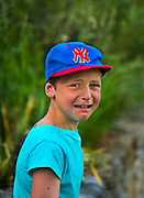 Boy wearing a New York baseball cap crying in the French countryside, 5th June 2016.
