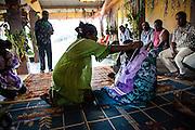 La femme s'offre à la mère de son époux sous le regard des hommes. Ce moment marque l'instant précis du mariage qui lie les liens des deux clans. La femme quitte son clan pour rejoindre celui de son mari. Elle revêt alors sa future « maman » d'une robe et lui offre un sac dans lequel se trouvent les outils qui serviront à son travail de femme et d'épouse. Cérémonie coutumière de mariage – Huiwatrul, Grande chefferie de Lössi, Lifou, Îles Loyauté, Nouvelle-Calédonie - Avril 2014
